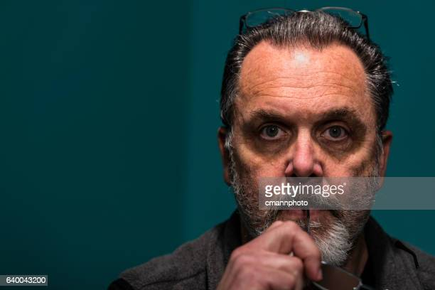 portrait of middle-aged man thinking and biting eyeglasses. - cmannphoto stock pictures, royalty-free photos & images