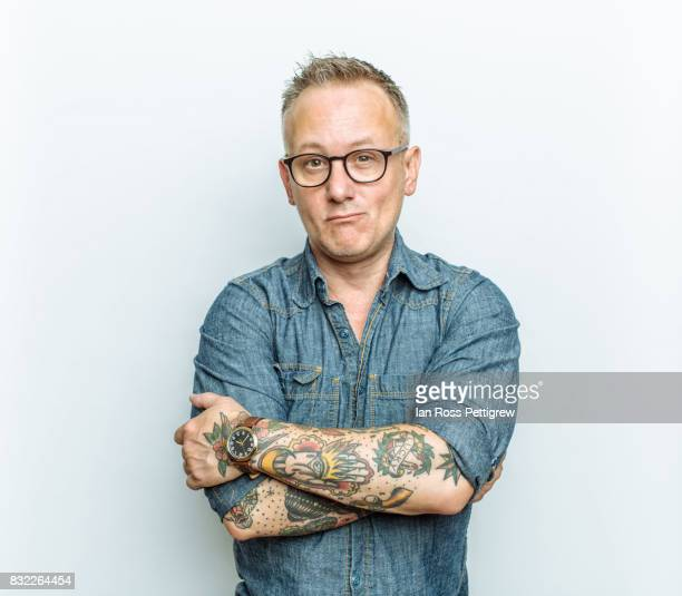 portrait of middle-aged man with tattoos - oberkörperaufnahme stock-fotos und bilder