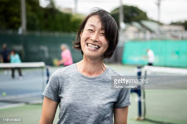 portrait of middle-aged woman enjoying tennis - muster ストックフォトと画像