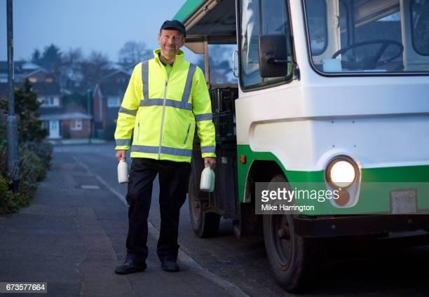 Portrait of Milkman holding milk bottles by his van