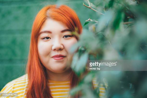 portrait of millennial generation young woman wearing yellow t-shirt in fron of green wall - curvy asian woman stock pictures, royalty-free photos & images