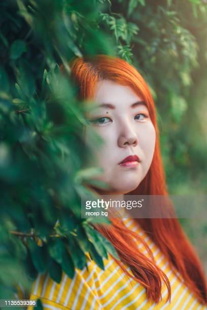portrait of millennial generation young woman wearing yellow t-shirt - curvy asian woman stock pictures, royalty-free photos & images