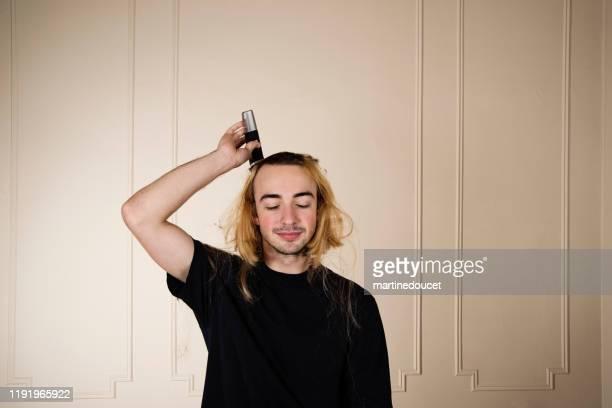 """portret van duizendjarige jonge man het scheren van zijn haar. - """"martine doucet"""" or martinedoucet stockfoto's en -beelden"""
