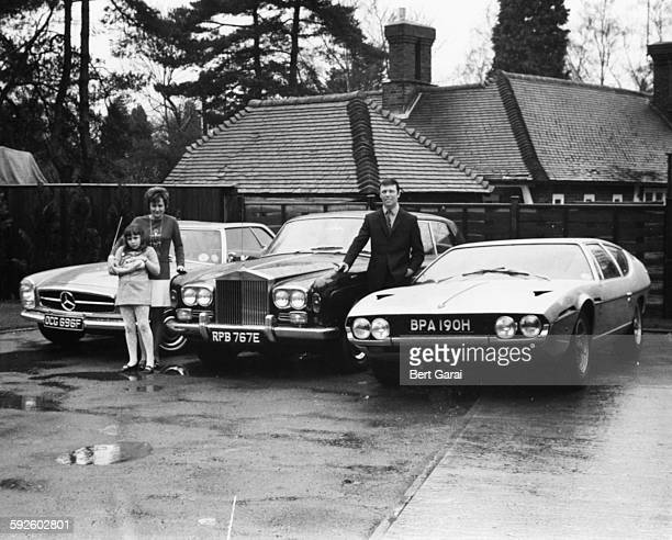 Portrait of millionaire song writer Les Reed and his three luxury cars including his new Lamborghini with his wife and daughter Donna who is holding...