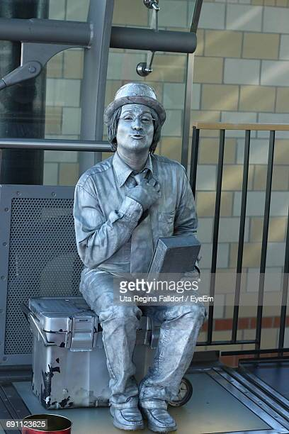 portrait of mime painted in silver sitting on box against wall - mime stock photos and pictures