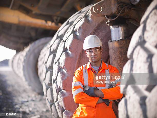 Portrait of miner standing next to  dumper truck tyres in opencast coalmine