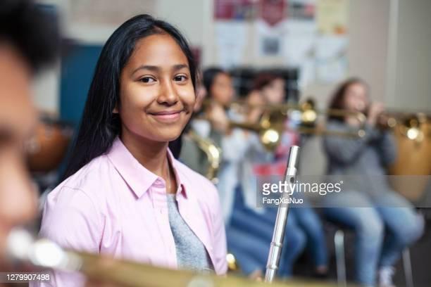 バンドオーケストラクラスでフルートを持つ混合民族のアジアの女の子の肖像 - ブラスバンド ストックフォトと画像