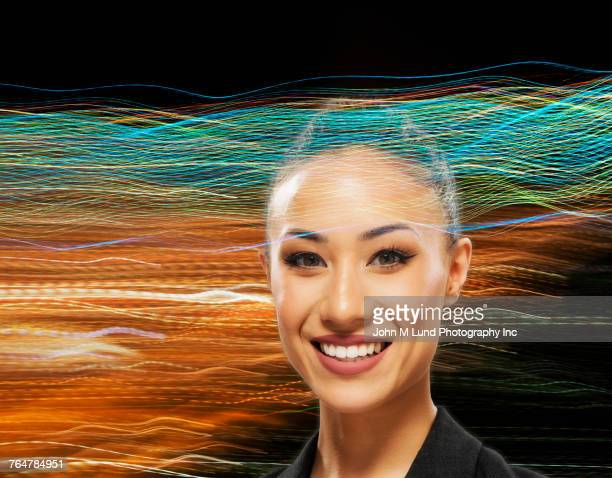 Portrait of mixed race businesswoman in internet waves