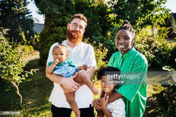 portrait of mixed race family in garden - origine ethnique photos et images de collection