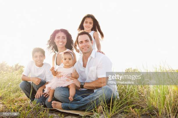 portrait of mixed race family sitting in grass - perfektion stock-fotos und bilder