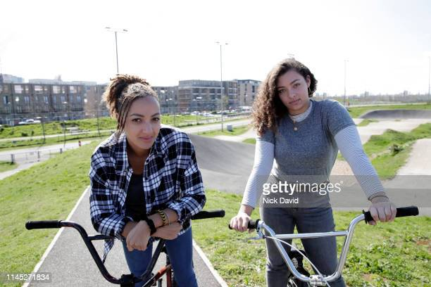 portrait of mixed race friends on bmx bikes in skate park - bmx track london stock pictures, royalty-free photos & images