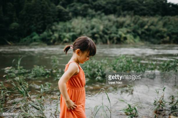 Portrait of mixed race little girl by river