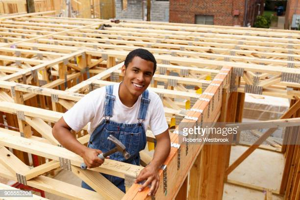 Portrait of mixed race man hammering nail at construction site
