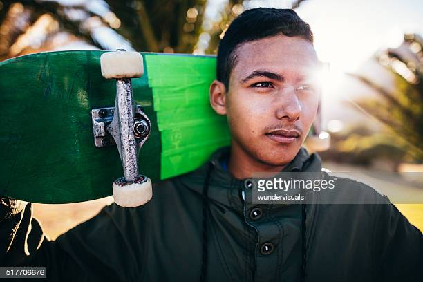 Portrait of Mixed Race Person Holding Skateboard Behind Head