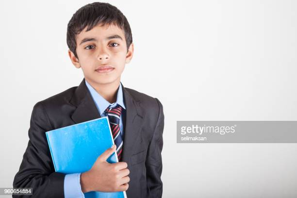 Portrait Of Mixed Race Schoolboy Holding Book