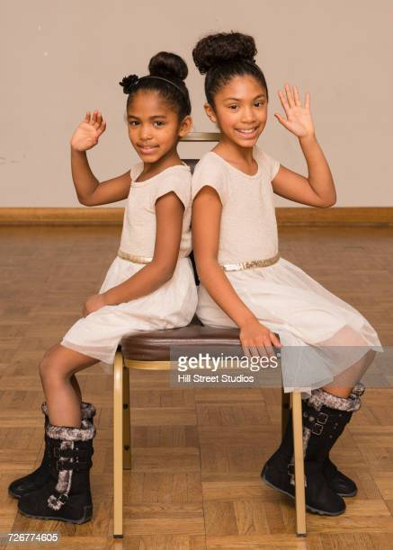 Portrait of Mixed Race sisters waving sitting back to back on chair