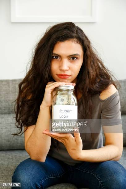 Portrait of mixed race woman holding jar of money for student loan