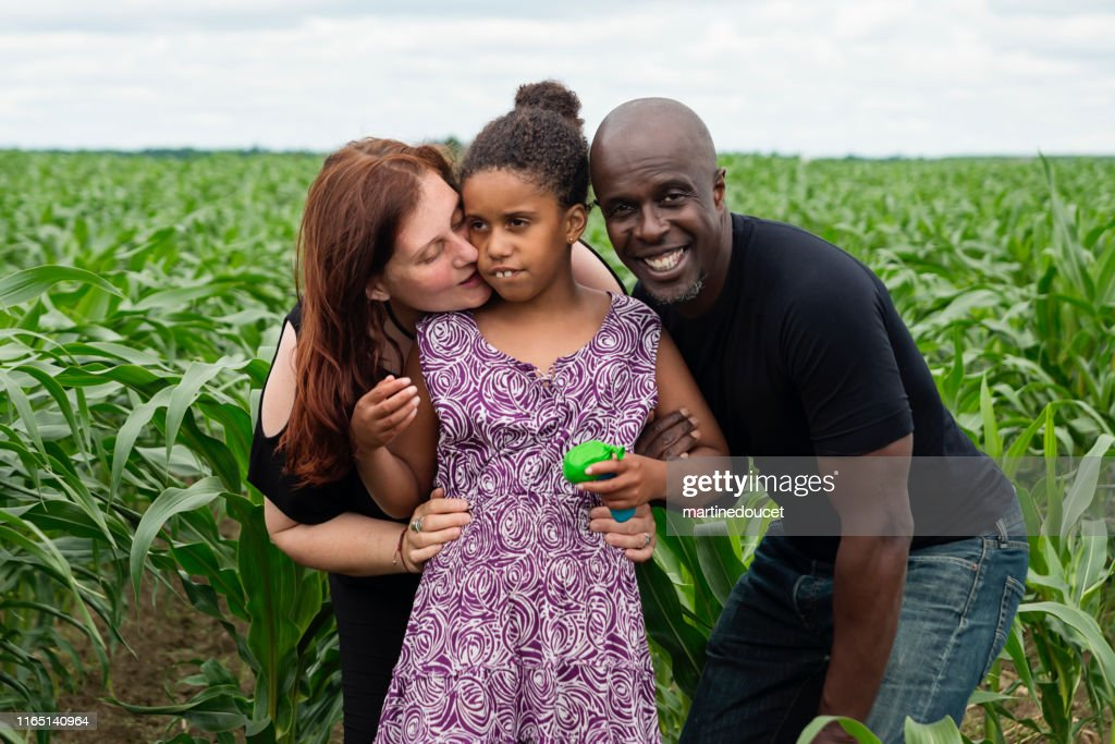 Portrait of mixed-race family with autist daughter in nature. : Stock Photo