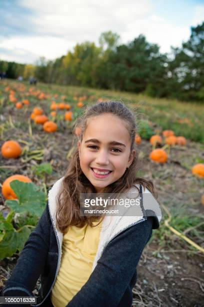 """portrait of mixed-race little girl in a pumpkin patch. - """"martine doucet"""" or martinedoucet stock pictures, royalty-free photos & images"""