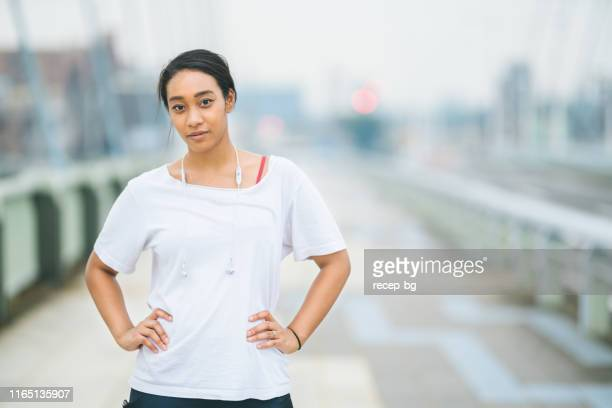 a portrait of mixed-race woman in sports clothing - ethnicity stock pictures, royalty-free photos & images