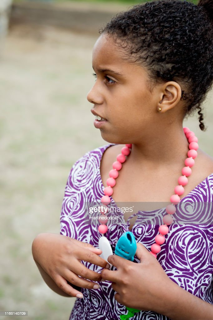 Portrait of mixed-race young girl with autism outdoors. : Stock Photo