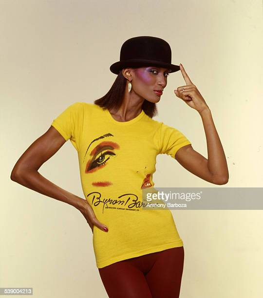 Portrait of model Beverly Johnson dressed in bright yellow Byron Barnes print tshirt and a bowler hat New York 1980s
