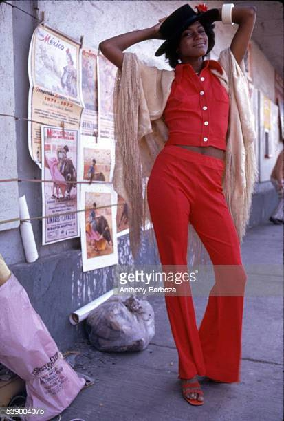 Portrait of model Carol Hobbs as she poses on a sidewalk dressed in bright red top and trousers a tan shawl over her shoulders and a bolero hat on...