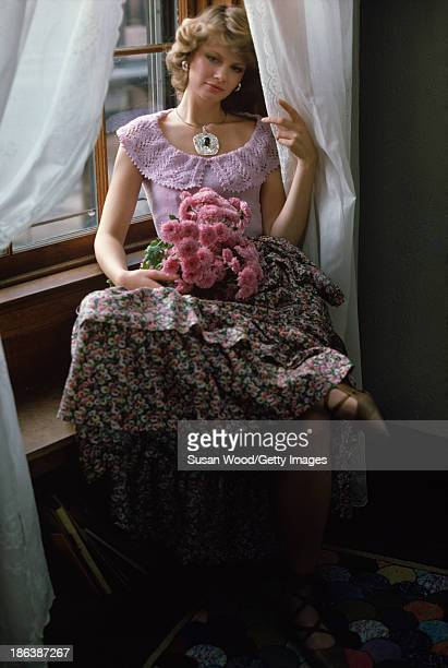 Portrait of model dressed in a crocheted lilac top and a floral skirt as she sits in a window seat a bouquet of pink flowers in her lap November 1972...