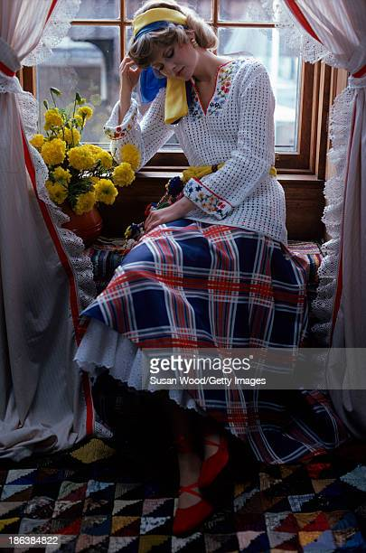 Portrait of model dressed in a crocheted white sweater with floral applique and a plaid skirt with white petticoat as she sits in a window seat...