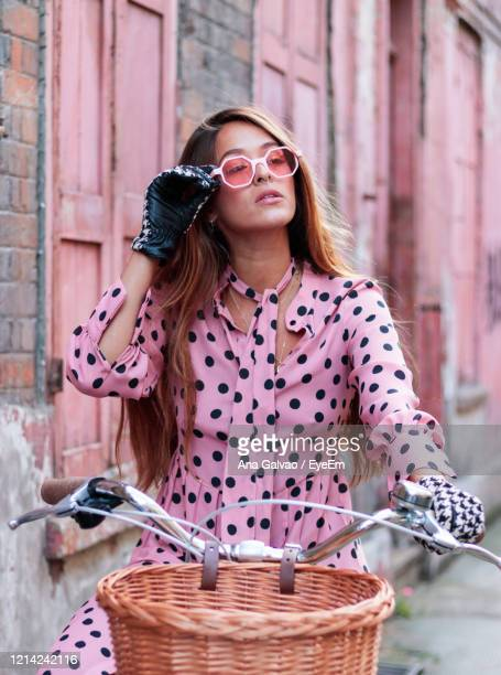 portrait of model in pink dress and gloves on a bicycle in london - street style stock pictures, royalty-free photos & images