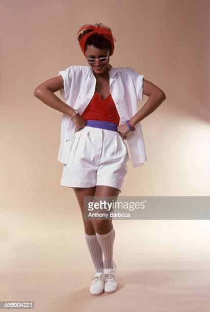 Portrait of model Sheila Johnson as she poses in summer fashion New York 1970s She wears a red shirt under a white shirt white shorts socks and shoes...