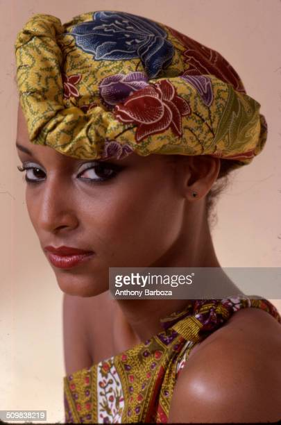Portrait of model Sheila Johnson dressed in a print top and matching fabric headpiece New York 1970s
