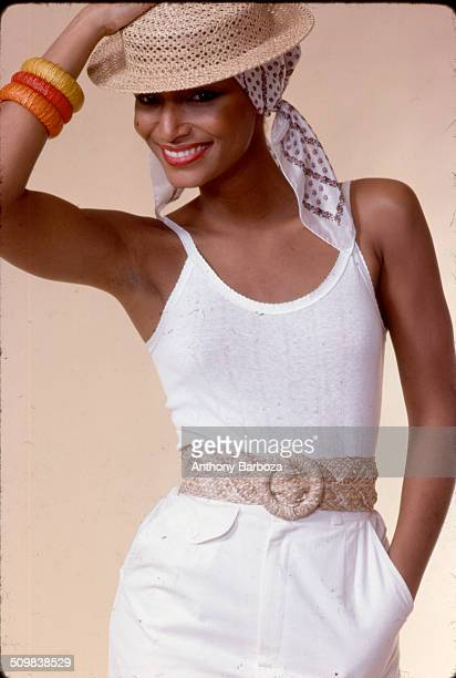 Portrait of model Sheila Johnson dressed in a white tank top and straw hat New York 1970s