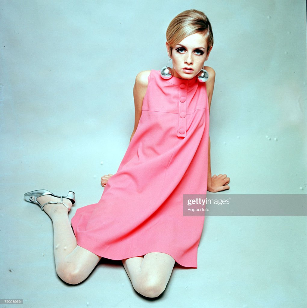 1966. A portrait of model Twiggy sitting on a studio floor wearing a pink fashionable dress and large silver bauble earrings whilst looking at the camera. : News Photo