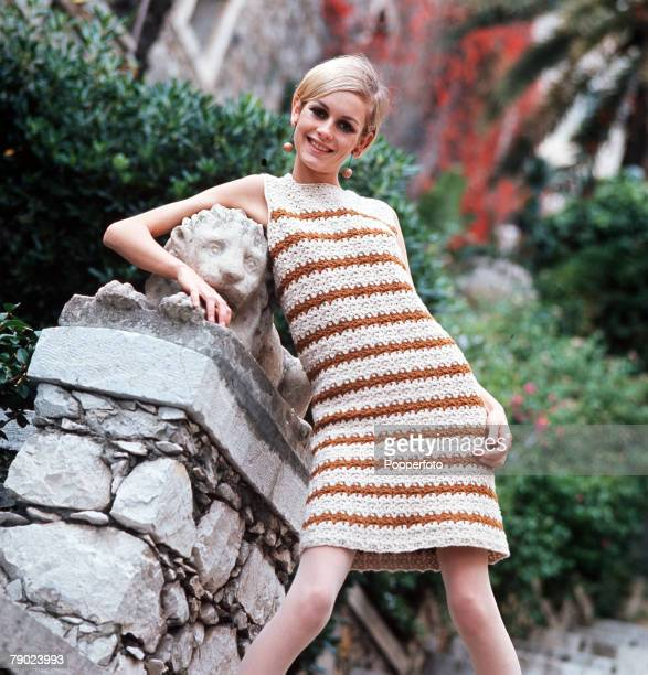 Portrait of model Twiggy wearing a fashionable dress whilst posing with her arm around a stone lion smiling at the camera