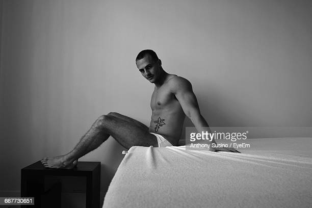Portrait Of Model Wearing Underwear While Sitting On Bed Against Wall