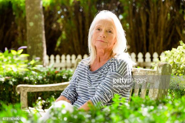 Portrait of modern, attractive mature woman sitting in the park