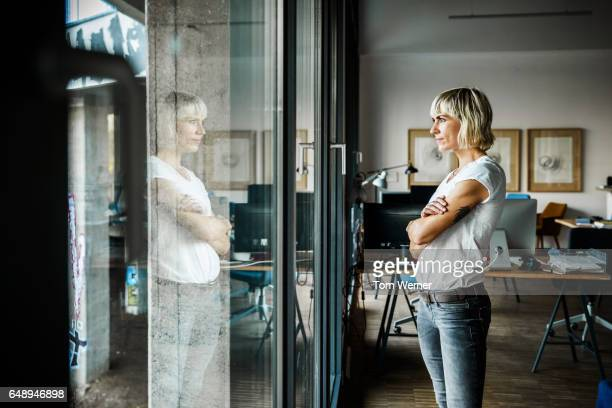 portrait of modern businesswoman standing in her office - introspection stock pictures, royalty-free photos & images