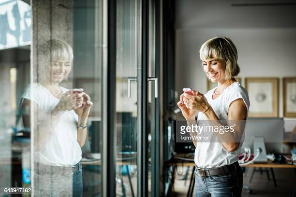 Portrait of modern businesswoman with smart phone in her office