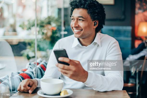 portrait of modern man with wireless earbuds in a cafe - bluetooth stock pictures, royalty-free photos & images