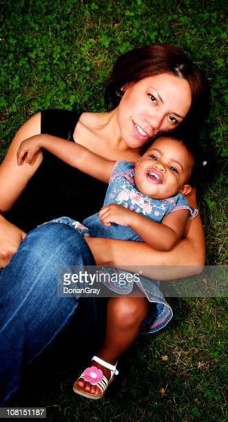 portrait of mother and baby daughter lying in grass - black ginger baby stock photos and pictures
