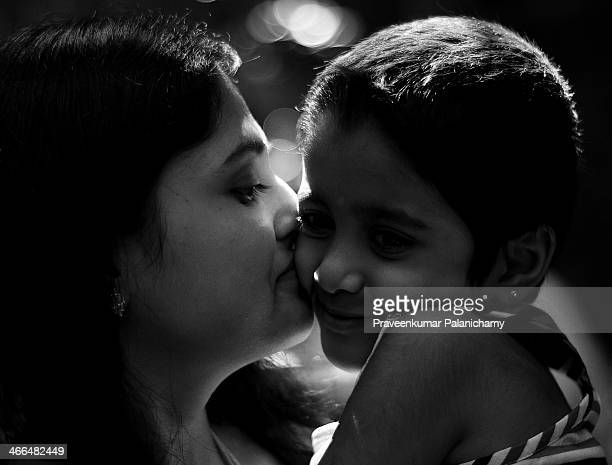portrait of mother and child - indian girl kissing stock photos and pictures