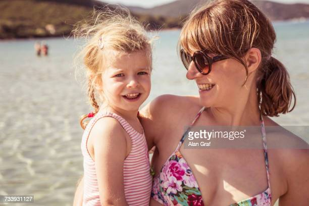 Portrait of mother and daughter at beach, smiling