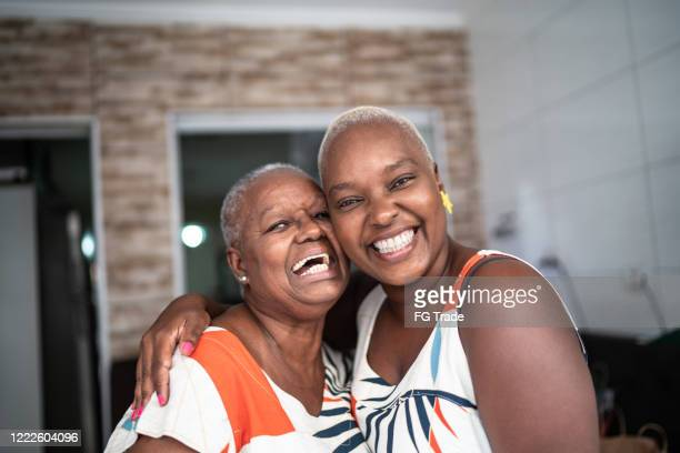 portrait of mother and daughter at home - mid adult women stock pictures, royalty-free photos & images