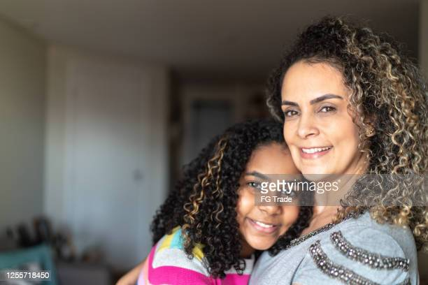 portrait of mother and daughter embracing - latin american and hispanic ethnicity stock pictures, royalty-free photos & images