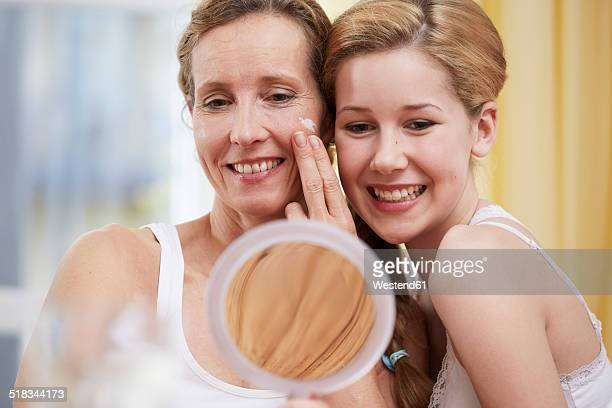 portrait of mother and daughter heat to head with handheld mirror - girl in mirror stock photos and pictures