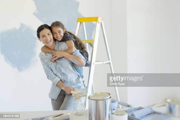Porträt von Mutter und Tochter Umarmen in der Nähe von Farbe Material