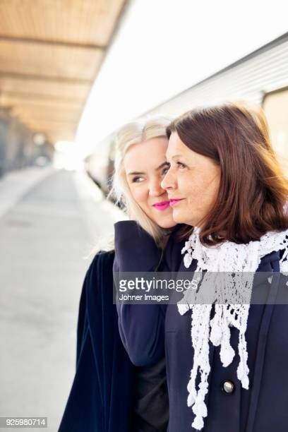 Portrait of mother and daughter hugging on train station