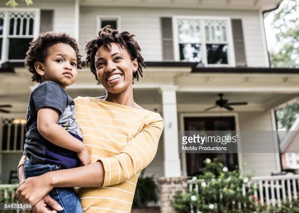 portrait of mother and daughter in front of home - home ownership stock pictures, royalty-free photos & images