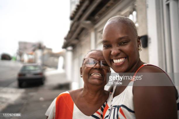 portrait of mother and daughter in front of they house - leanincollection stock pictures, royalty-free photos & images